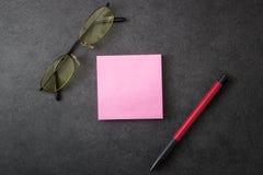 Klibbiga anmärkning, penna och exponeringsglas Arkivfoton