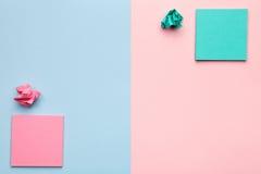 Klibbiga anmärkningar med smulade pappers- bollar på pastellfärgad bakgrund Arkivfoton
