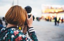 Klickar den turist- flickahållen för hipsteren i modern fotokamera för händer, tagandefotografi på ljus för defocusbakgrund royaltyfri foto