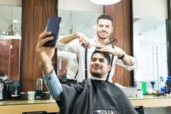 Klient Bierze Selfie Na telefonie Podczas gdy fryzjer męski Projektuje Jego włosy zdjęcia royalty free