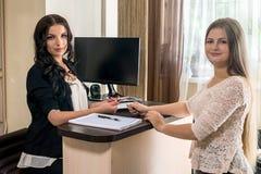 Klient daje jej karcie kredytowej administrator w piękno salonie zdjęcia stock