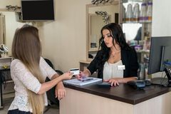 Klient daje jej karcie kredytowej administrator w pi?kno salonie fotografia royalty free