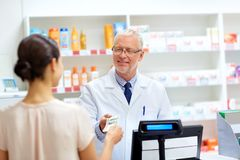 Klient daje pieniądze farmaceuta przy apteką zdjęcie stock