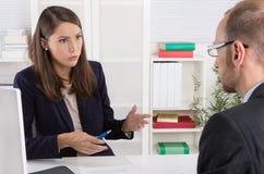 Klient i żeński pieniężny agent w dyskusi przy biurkiem Zdjęcia Royalty Free