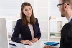 Klient i żeński pieniężny agent w dyskusi przy biurkiem Obrazy Stock