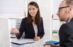 Klient i żeński pieniężny agent w dyskusi przy biurkiem Obrazy Royalty Free