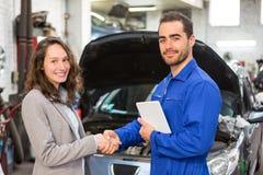 Klient i mechanik przy garażem Obrazy Stock