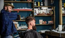 Klient i mistrzowski sprawdza rezultat ostrzyżenie lub Modnisia klient dostać nowego ostrzyżenie Ostrzyżenia pojęcie barber obraz stock