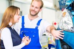 Klient i samochodowy mechanik w warsztacie zdjęcia stock