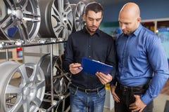 Klient i sprzedawca przy samochód usługa lub auto sklepem fotografia stock