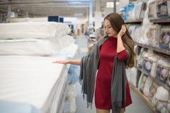 Klient kobieta wybiera łóżkową pościel w supermarketa centrum handlowego sklepie obraz stock