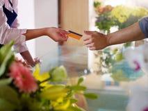 Klient mit dem Kreditkarteeinkaufen im Blumensystem stockfotografie