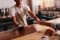 Klient płaci przez kredytowej karty przy sklep z kawą Obraz Royalty Free