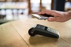 Klient płaci przez mądrze telefonu w sklep z kawą obraz stock
