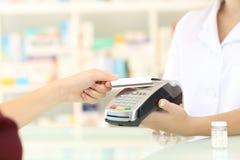 Klient płaci z kredytowym czytnikiem kart w aptece fotografia royalty free