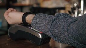 Klient płaci z NFC technologią mądrze zegarkiem contactless na terminal w nowożytnej kawiarni Obrazy Stock