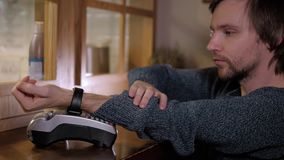Klient płaci z NFC technologią mądrze zegarkiem contactless na terminal w nowożytnej kawiarni Zdjęcia Royalty Free