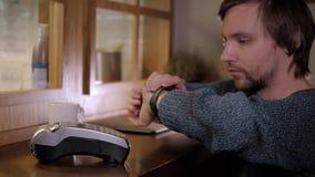 Klient płaci z NFC technologią mądrze zegarkiem contactless na terminal w nowożytnej kawiarni Zdjęcia Stock