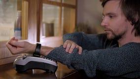 Klient płaci z NFC technologią mądrze zegarkiem contactless na terminal w nowożytnej kawiarni Zdjęcie Royalty Free