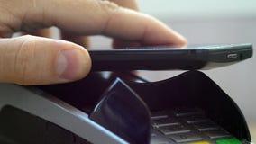 Klient płaci z NFC technologią telefonem komórkowym na POS terminal zdjęcie stock