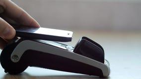 Klient płaci z NFC technologią telefonem komórkowym na POS terminal zdjęcia stock