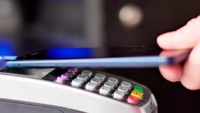Klient płaci z NFC technologią telefonem komórkowym na terminal zdjęcia stock