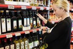 Klient Patrzeje Mądrze zegarek Podczas gdy Wybierający olej W Supermarke obrazy stock