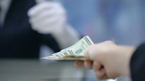 Klient som betalar pengar till hotelladministratören, incheckning på mottagandet, closeup arkivfilmer
