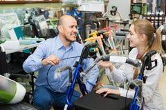 Klient som frågar flicka om elektriska rullstolar arkivfoton
