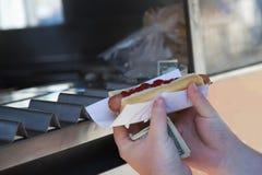 Klient trzyma hot dog nabywający Obrazy Royalty Free