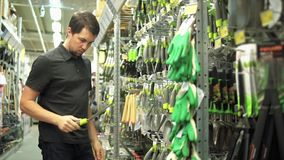 Klient w narzędzia sklepie dostaje zainteresowanym w małej ogrodowej łopacie zbiory