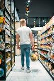 Klient wybiera jedzenie w supermarkecie z koszem obraz stock