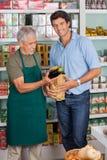 Klient Z sprzedawcy kładzenia warzywem W papierze Zdjęcie Stock