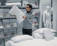 Klienta mężczyzna wybiera łóżkową pościel w supermarketa centrum handlowego sklepie zdjęcia stock