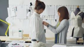 Klienten försöker på den nya skjortan i skräddare som ` s shoppar, medan sömmerskan kontrollerar format och kvalitet av plagget p lager videofilmer
