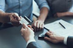 Klienten ger kreditkorten till konsulenten för auto försäljningar arkivfoton