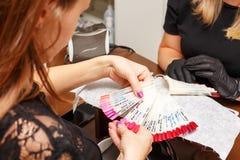 Klienten i salongen av manikyr väljer färgen av spikar polermedel royaltyfri fotografi