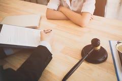 Klienten och advokaten har en framsida för sitta - - vänder mot ner möte för att diskutera det lagligt Royaltyfri Bild