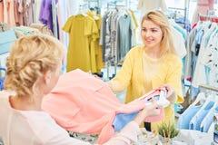 Klienten och säljaren i ett klädlager fotografering för bildbyråer