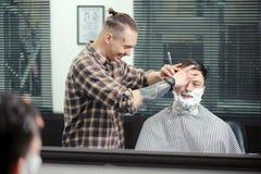 Klienten som rakar på barberaren, shoppar royaltyfri bild