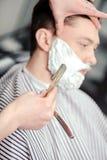 Klienten som rakar på barberaren, shoppar royaltyfri fotografi