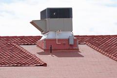 Klimaanlage auf einem Ziegeldach des roten Lehms eines Gebäudes stockfoto