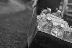 Klimaatverandering en wateraanbodtekortbedreigingen Het witte mannetje trekt een kar van plastic die flessen met schoon water wor stock foto