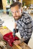 Klimaporträt des Mannes arbeitend in der Werkstatt mit Gitarre Stockfotografie