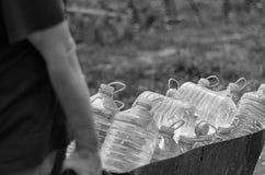 Klimatförändring- och vattenförsörjningbristhot Den vita mannen drar en vagn av plast- flaskor som fylls med rent vatten Royaltyfri Bild