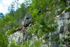 Klimmer die bovenop een berg met een veiligheid beklimmen Royalty-vrije Stock Fotografie