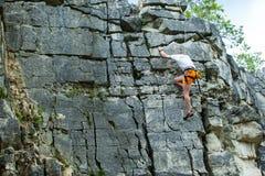 Klimmer die bovenop een berg met een veiligheid beklimmen Stock Fotografie