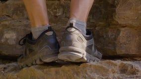 Klimmerbenen in trekkingslaarzen die aan rotsachtige berg beklimmen terwijl reis Mannelijke voet in trekkingsschoenen die aan kli stock video