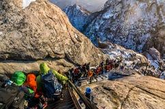 Klimmers die een steile die helling oversteken met sneeuw wordt behandeld Stock Afbeelding