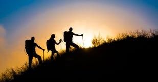Klimmers op grasrijke heuvel Stock Foto's